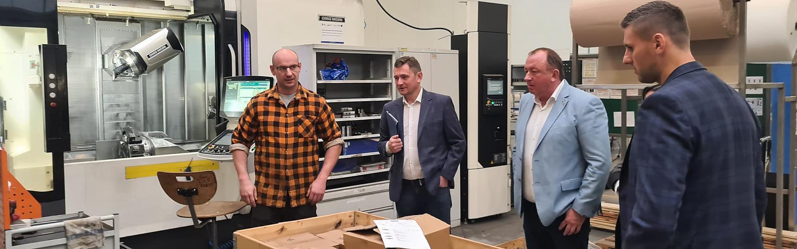 Wicemarszałek województwa Tomasz Sobieraj (w środku) i prezes firmy Inter-Metal Tomasz Maksymiuk (błękitna marynarka) na hali produkcyjnej.